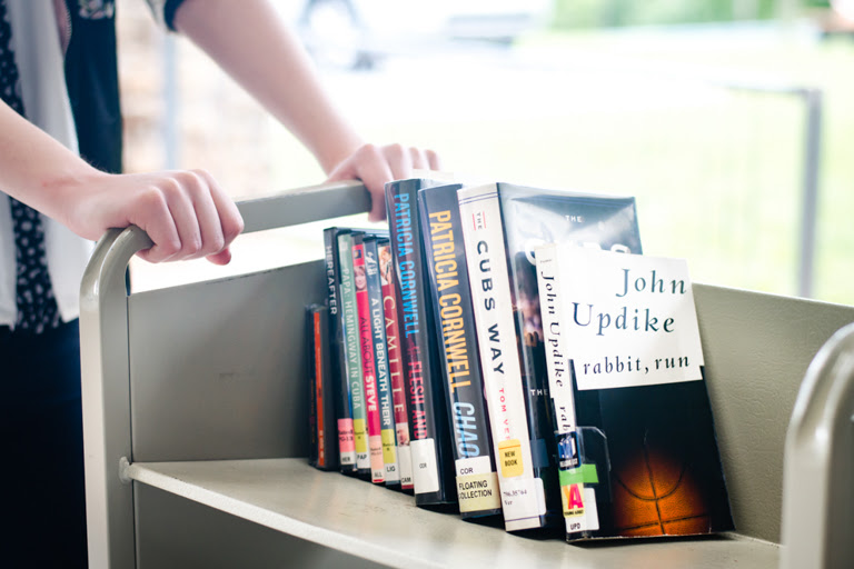 volunteer pushing book cart