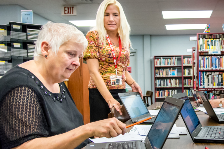 library staff helping woman on computer