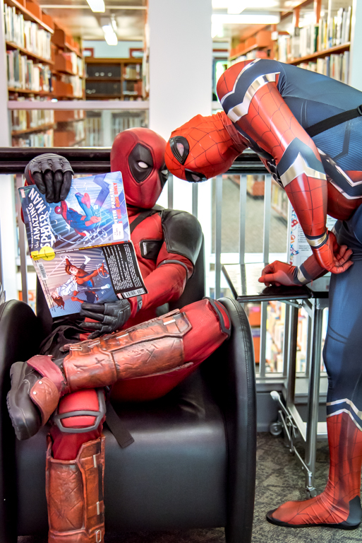 Deadpool and Spiderman looking at comic