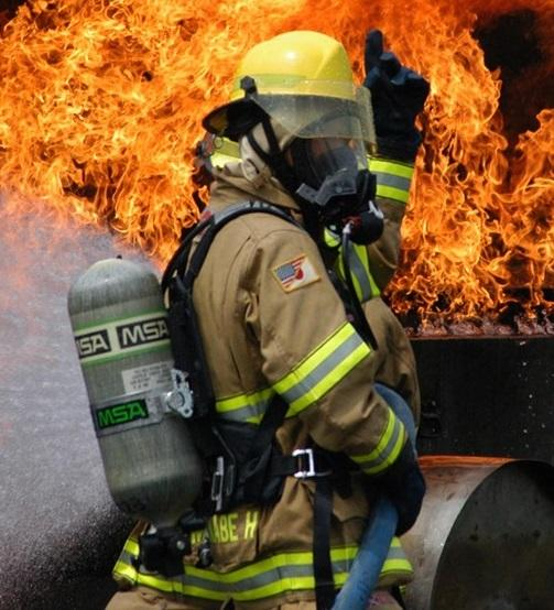 firefighter standing in front of flames with fire gear on